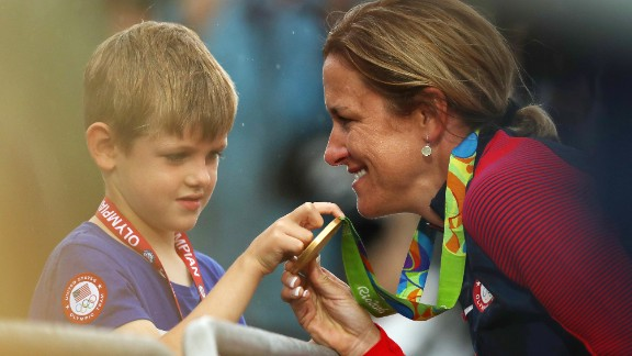 American cyclist Kristin Armstrong shows her gold medal to her son, Lucas, after winning the time trial for the third straight Olympics. Williams won the event a day before turning 43 years old. She was the oldest woman in the field by seven years.