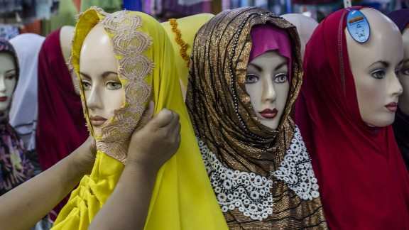 Hijab: The scarf worn tightly around the head and neck does not cover the face. It is the most common Islamic head covering. This Indonesian girl is shopping for a hijab in Yogyakarta.