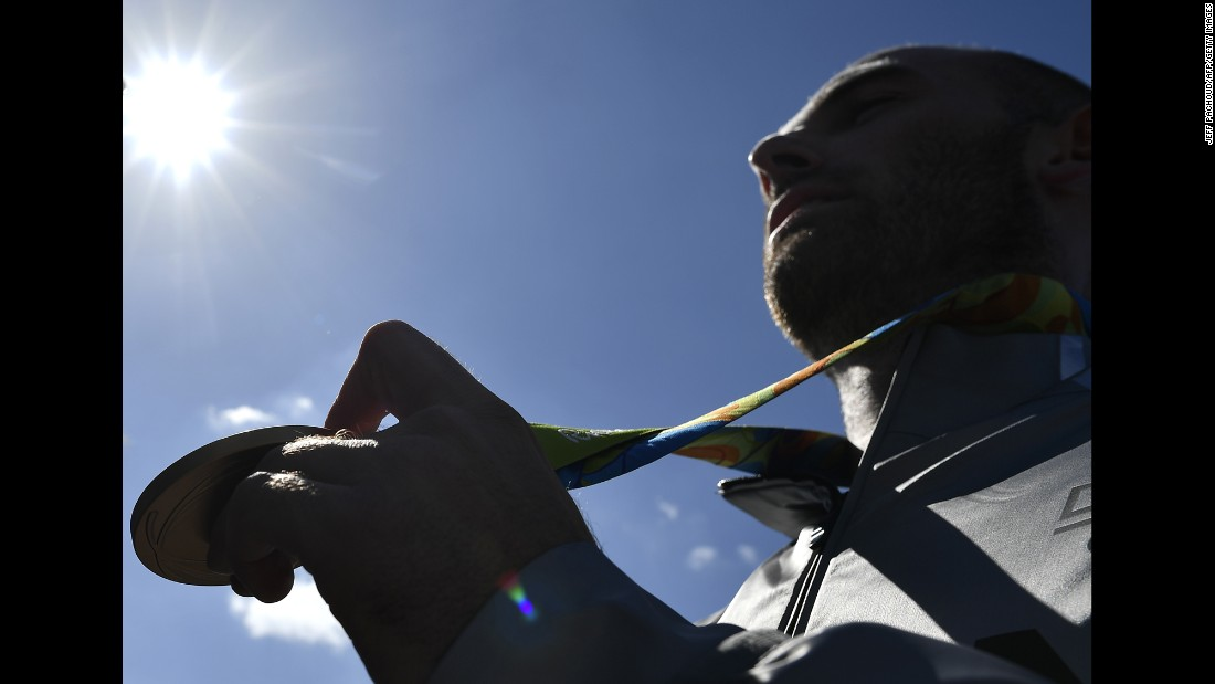 German rower Karl Schulze celebrates with his gold medal after winning the quadruple sculls competition.