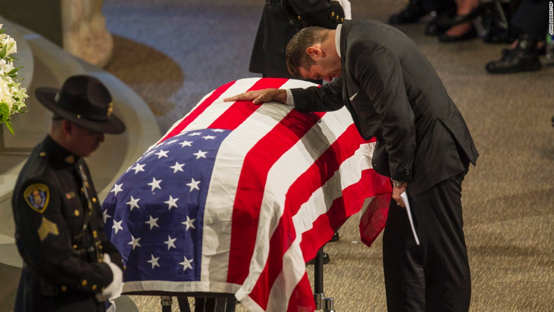 "San Diego Police Sgt. John Iammarino, who worked closely with Jonathan De Guzman, leans on De Guzman's coffin during a memorial service Friday, August 5, in El Cajon, California. De Guzman, 43, <a href=""http://www.cnn.com/2016/07/29/us/san-diego-police-officers-shot/"" target=""_blank"">was fatally shot last month</a> in the line of duty."