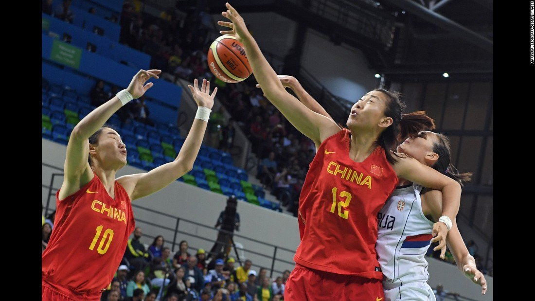 China's Lu Wen, left, and Gao Song compete for a rebound with Serbia's Sonja Petrovic.