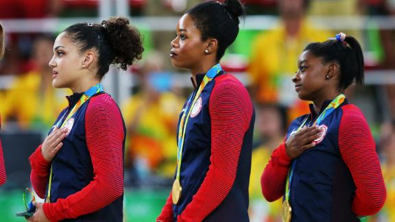 RIO DE JANEIRO, BRAZIL - AUGUST 09:  (R to L) Gold Medalists Simone Biles, Gabrielle Douglas, Lauren Hernandez, Madison Kocian and Alexandra Raisman of the United States stand on the podium for the national anthem at the medal ceremony for the Artistic Gymnastics Women