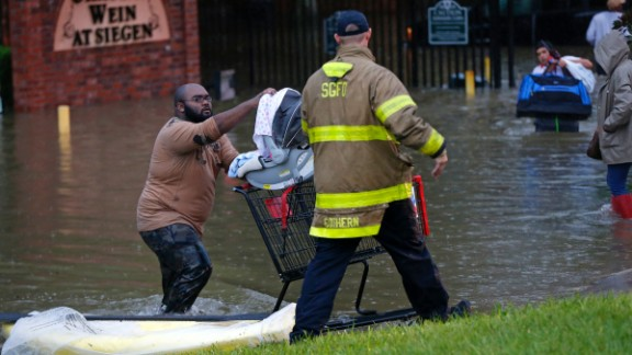 A firefighter helps a resident in Baton Rouge on Friday, August 12.