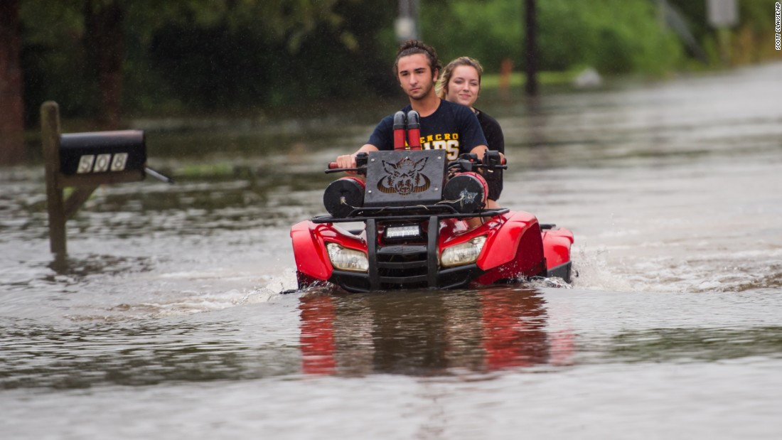 People ride an all-terrain vehicle through a flooded neighborhood in Carencro, Louisiana, on August 13.
