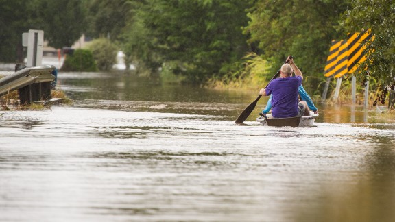 Jeremy and Chelsea LeMieux paddle through floodwaters in Carencro on August 13.