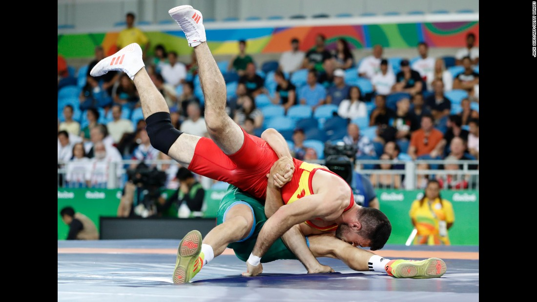 Colombia's Carlos Andres Munoz Jaramillo, in red, is pulled to the ground by Hungary's Peter Bacsi in their men's 75kg greco-roman qualification match during the wrestling event.