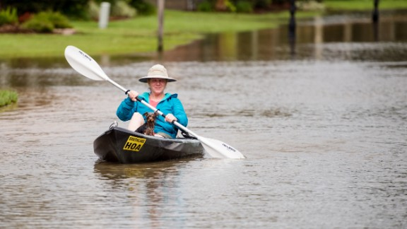 Jennifer Bernard and her dog, Shelby, travel by kayak down the flooded streets of Youngsville on August 14.