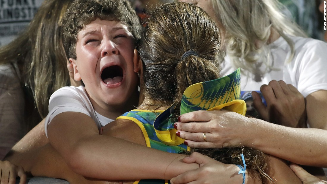 Brazil's Larissa Franca, center, is hugged by supporters after reaching the semifinals of the women's beach volleyball tournament with partner Talita Antunes.