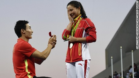 Silver medallist China's He Zi (R), reacts she receives a marriage proposal from Chinese diver Qin Kai during the podium ceremony of the Women's diving 3m Springboard Final at the Rio 2016 Olympic Games at the Maria Lenk Aquatics Stadium in Rio de Janeiro on August 14, 2016.   / AFP / CHRISTOPHE SIMON        (Photo credit should read CHRISTOPHE SIMON/AFP/Getty Images)