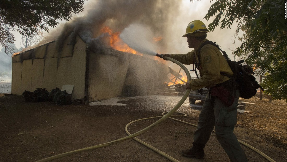 Tyrol Martin of the US Forest Service douses flames as a structure burns near the town of Lower Lake, California on Sunday, August 14. Flames continue to burn out of control in the area. A wildfire destroyed at least four homes and forced thousands of people in two Northern California towns to flee on Sunday as flames jumped a road and moved into populated areas.