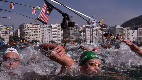 Refreshment bottles are held over women competing in the 10-kilometer open water swimming event.