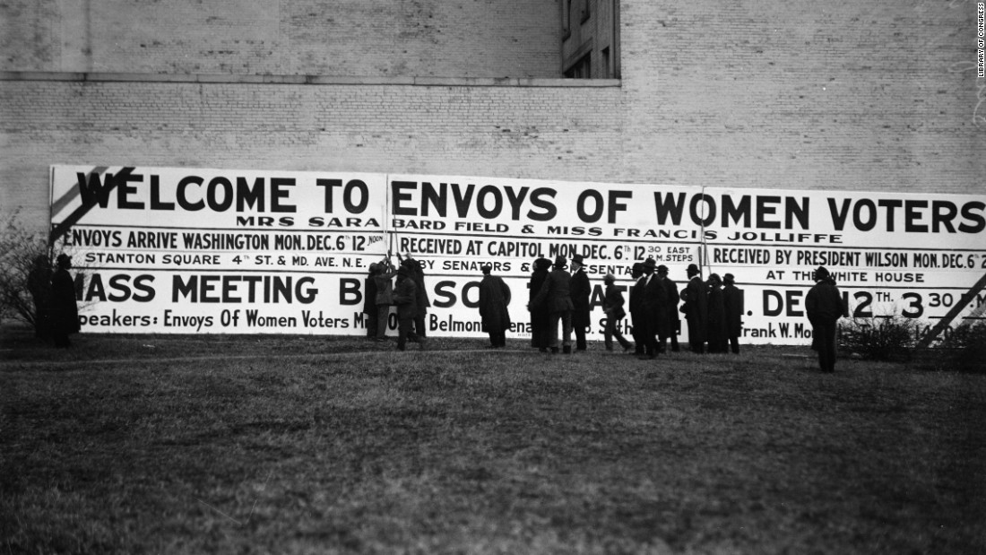 After the march, people mill around a pro-suffrage sign in Washington.