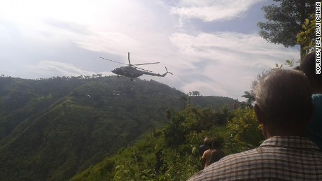 A helicopter lifts off from the mountainous site of a bus crash in Nepal.