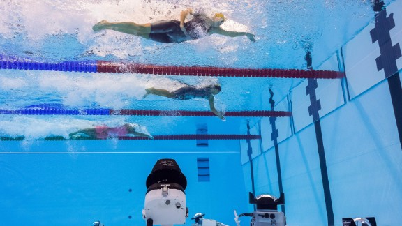 Cameras are set up at the bottom of the swimming pool as women take part in a 50-meter freestyle heat on Friday, August 12. Catching the Olympic moments that TV doesn't