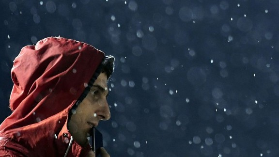 A fan watches the archery competition in pouring rain on Wednesday, August 10.