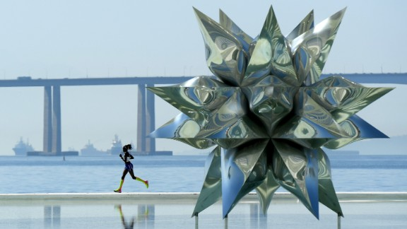 A woman runs by the Puffed Star II sculpture during the Olympic marathon on Sunday, August 14.