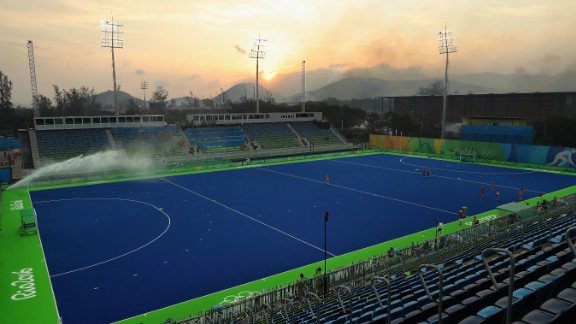 A wildfire burns in hills near the field hockey venue before a quarterfinal match between Great Britain and Spain.