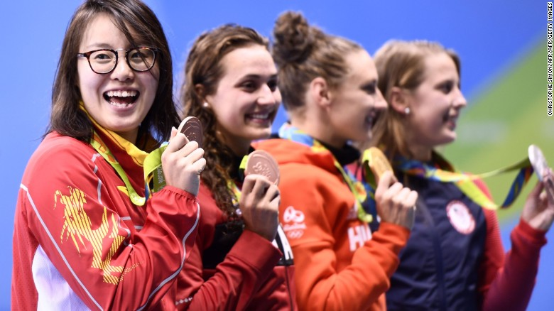 Hungary's Katinka Hosszu (2ndR) celebrates with silver medallist USA's Kathleen Baker (R) and equal bronze medallists Canada's Kylie Masse (2ndL) and Chinese's Fu Yuanhui on the podium after she won the Women's 100m Backstroke Final during the swimming event at the Rio 2016 Olympic Games at the Olympic Aquatics Stadium in Rio de Janeiro on August 8, 2016.   / AFP / CHRISTOPHE SIMON        (Photo credit should read CHRISTOPHE SIMON/AFP/Getty Images)