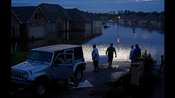 Residents evacuate Hammond, Louisiana, with food in ice chests on Saturday, August 13.