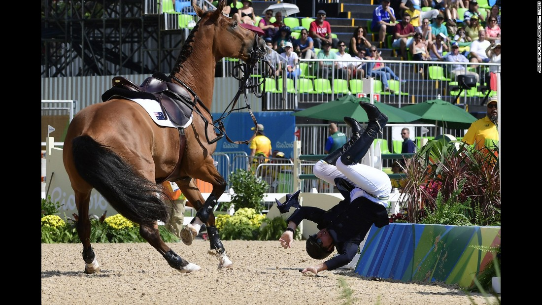 Australian equestrian Scott Keach falls off his horse, Fedor, during the individual jumping competition.
