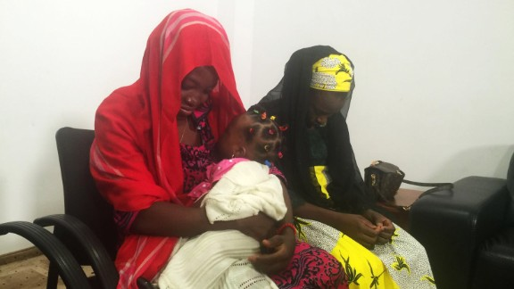 Chibok girl Amina Ali Nkeki (in red), who was kidnapped by Boko Haram and escaped after two years, with her baby and friend Serah Luka.
