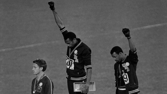 """** FILE ** In this Oct. 16, 1968, file photo, United States athletes Tommie Smith, top center, and John Carlos, top right, extend their gloved fists skyward during the playing of the """"Star-Spangled Banner"""" after Smith received the gold and Carlos the bronze for the 200-meter run at the Summer Olympic Games in Mexico City. Carlos and Smith raised their black-gloved fists on the medals stand as a symbol of protest 40 years ago at the Mexico City Olympics, creating an iconic image from the games. Australia's silver medalist Peter Norman is at left.  (AP Photo/file)"""