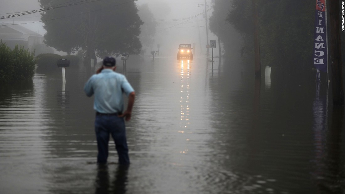 Gary Schexnayder stands in a flooded street in Sorrento as an early morning fog blankets the area August 17.