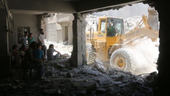 Syrians shelter in a damaged building as civil defence workers sift through debris looking for survivors following reported air strikes on July 14, 2016 in Aleppo's rebel-held neighbourhood of Tariq al-Bab.  Nine people were killed in the Tariq al-Bab area, and another three in the district of Salhin, both in eastern Aleppo, the Syrian Observatory for Human Rights reported. The Britain-based group said it was unclear whether the strikes were carried out by warplanes of the Syrian government or its ally Russia.   / AFP / THAER MOHAMMED        (Photo credit should read THAER MOHAMMED/AFP/Getty Images)
