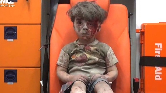 Omran Daqneesh, bloodied and covered with dust, sits in an ambulance after a strike in August.