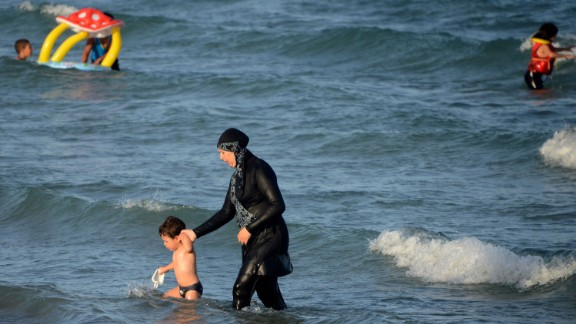 Burkini: The full-body swimsuit worn by Muslim women leaves only the face, hands and feet exposed. Here a woman in a burkini wades in the water with a child at Ghar El Melh beach in Tunisia.