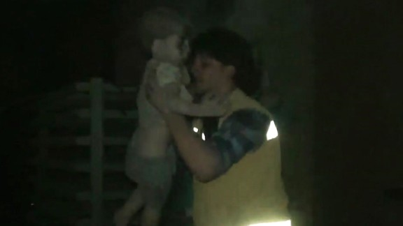 A civil defense worker carries Omran into the ambulance. The airstrike destroyed Omran