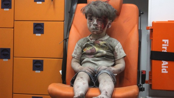 2016: Aleppo, Syria -- Five-year-old Omran Daqneesh waits shell-shocked in the back of an ambulance. He and other members of his family were injured when airstrikes ripped through his neighborhood in August. The photo inspired international grief and put a face on Syria