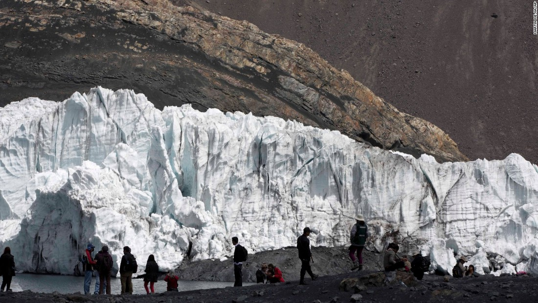 "Tourists walk in front of the Pastoruri glacier in Huaraz, Peru, during a tour called ""The Route of Climate Change"" on Friday, August 12."