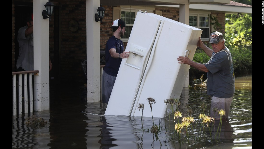 "Baron Leblanc, left, and George Snyder move a refrigerator out of George's flooded home in St. Amant on Thursday, August 18. More than 30,000 people have been rescued in southern Louisiana after heavy rains caused flooding. ""This is a major disaster,"" Louisiana Gov. John Bel Edwards has said."