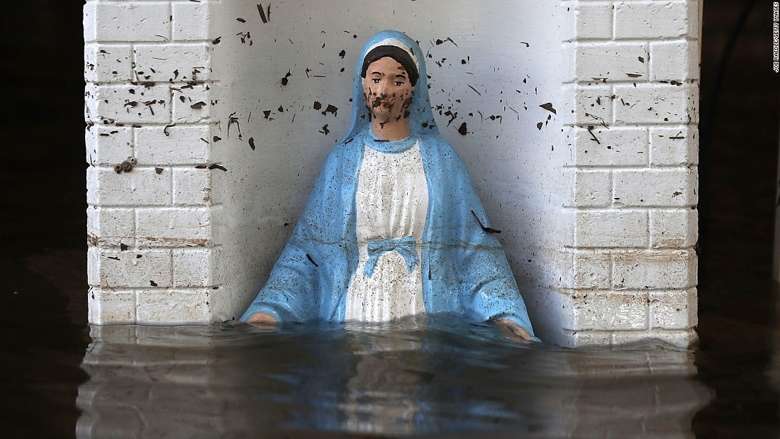 A Virgin Mary statue is barely visible in front of a flooded home in St. Amant on August 18.