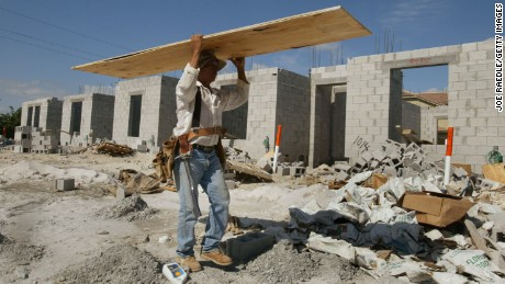 An immigrant worker carries plywood as he works on new homes May 7, 2004 in Homestead, Florida. Congressional Democrats rallied May 6 on Capitol Hill to introduce the Safe, Orderly Legal Visas and Enforcement Act, or SOLVE. The bill would offer green cards and potential U.S. citizenship to millions of undocumented workers in and out of agriculture.