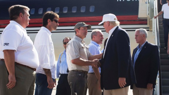 Republican presidential candidate Donald Trump, followed by his running mate, Indiana Gov. Mike Pence, shakes hands with Louisiana Attorney General Jeff Landry as he is greeted by Louisiana officials upon his arrival at the Baton Rouge airport in Baton Rouge, La., Friday, Aug. 19, 2016.