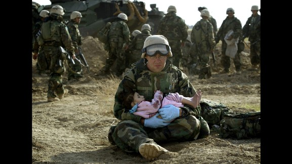 2003: Central Iraq -- A U.S. Navy hospital corpsman holds an Iraqi boy. Confused front-line crossfire ripped apart an Iraqi family. This moment of compassion was captured barely a year after the official start of the U.S.-led war in Iraq.