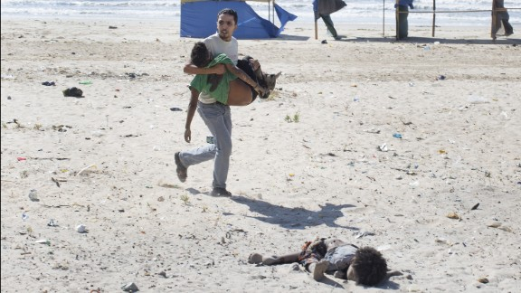 "2014: Gaza City -- A man carries a child as another lies dead after an Israeli airstrike on a Gaza City beach in July 2014. At least four boys, ages 9 to 11, were killed. The Israeli military investigated the tragedy and reported that the location of the attack was known to be a compound of Hamas police and naval forces. ""Tragically, in the wake of the incident it became clear that the outcome of the attack was the death of four children who had entered the military compound for reasons that remain unclear,"" the report stated."