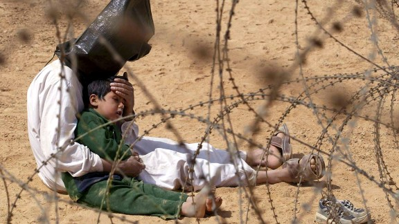 2003: Najaf, Iraq -- An Iraqi prisoner of war comforts his son in a POW holding zone. The emotional image won the 2003 World Press Photo award.