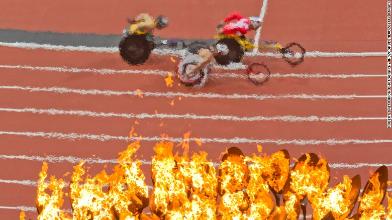 The Paralympic flame burns while wheelchair runners in the 5000 meters roll past as competition continues on the second day of the 2012 London Paralympics. China leads initial gold medal count with 34 gold medals while Australia totals 19 and the U.S. a distant sixth with 11 medals. (Photo by Robert Daemmrich Photography Inc/Corbis via Getty Images)