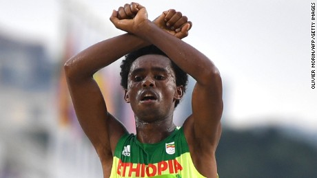 Ethiopia's Feyisa Lilesa crosses his arms at the finish line of the Men's Marathon event as a protest against the Ethiopian government's crackdown on political dissent.