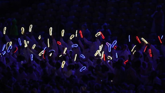 Members of Team Great Britain hold up their illuminated shoes.