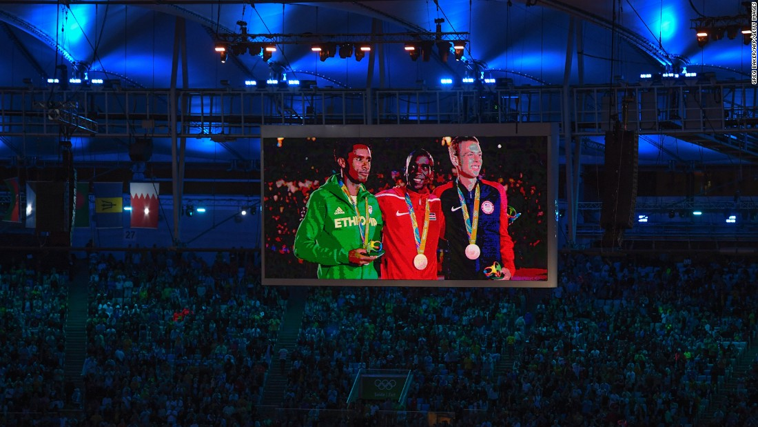 From left, men's marathon silver medalist Feyisa Lilesa of Ethiopia, gold medalist Eliud Kipchoge of Kenya and bronze medalist Galen Rupp of the United States are seen on a giant screen as they stand on the podium during the closing ceremony.