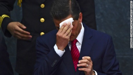 Mexican President Enrique Pena Nieto cleans his face next to Richard Kramer (out of frame), the president and chief executive officer of The Goodyear Tire & Rubber Company, during the announcement of an investment of 500 million US dollars in Mexico, on April 24, 2015, at Los Pinos presidential residence, in Mexico City. The US manufacturer of tyres Goodyear announced Friday an investment of about $500 million for the construction of a new plant in Mexico, the biggest producer of cars in Latin America. AFP PHOTO/RONALDO SCHEMIDT        (Photo credit should read RONALDO SCHEMIDT/AFP/Getty Images)