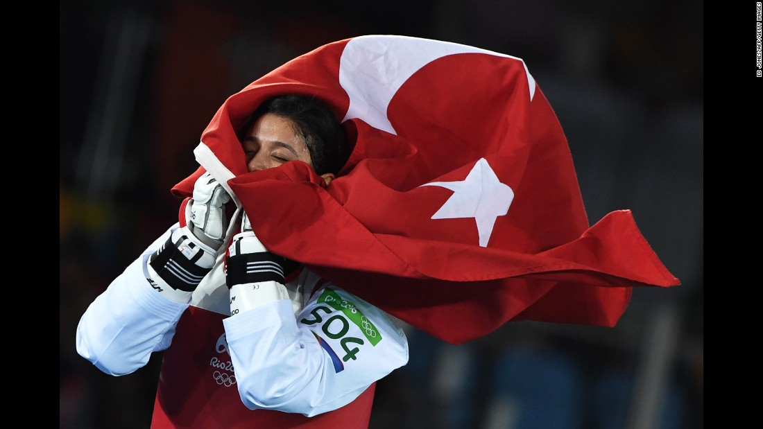Nur Tatar celebrates with the Turkish flag after winning a bronze medal in taekwondo on Friday, August 19.