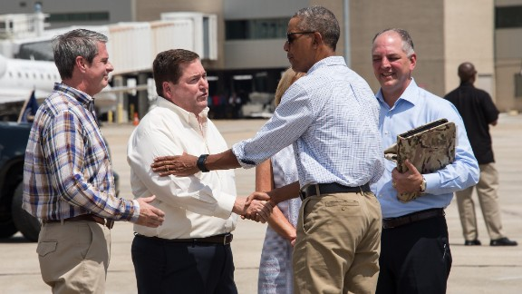 President Barack Obama is greeted by Louisiana Lt. Gov. Billy Nungesser as Gov. John Bel Edwards, right, his wife, Donna, and Sen. David Vitter, left, look on at Baton Rouge Metropolitan Airport in Baton Rouge, Louisiana, on August 23, 2016.