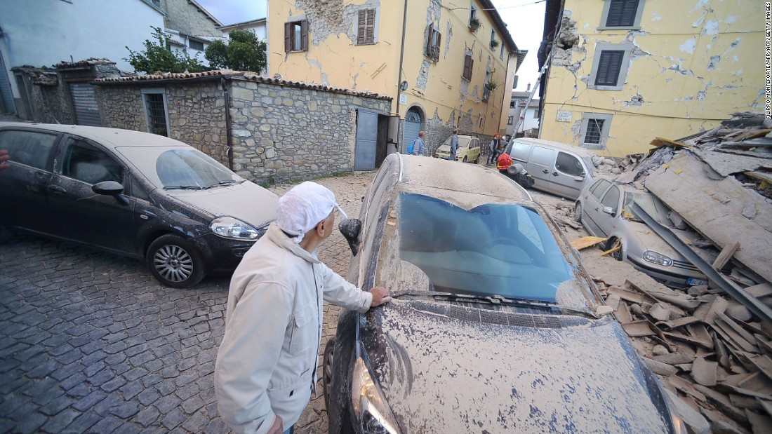 A man surveys damage near a dust-covered car in Amatrice on August 24.