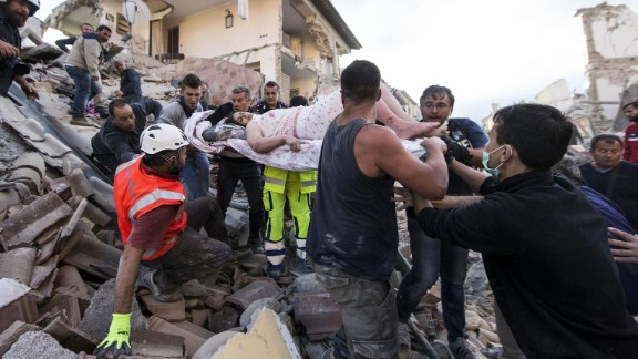A woman is pulled out of the rubble following an earthquake in Amatrice Italy, Wednesday, Aug. 24, 2016.  The magnitude 6 quake struck at 3:36 a.m. (0136 GMT) and was felt across a broad swath of central Italy, including Rome where residents of the capital felt a long swaying followed by aftershocks. (Massimo Percossi/ANSA via AP)