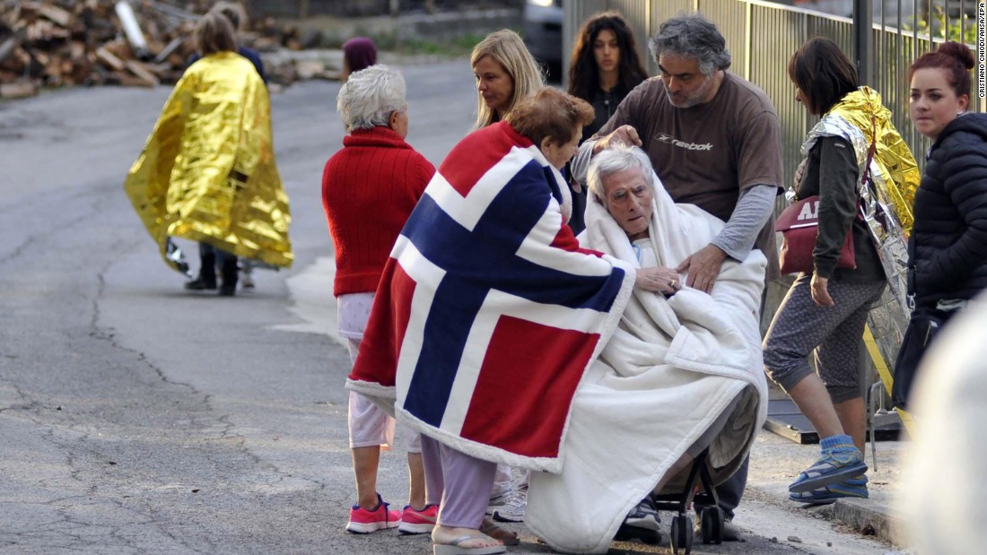 Residents of Pescara del Tronto care for an elderly earthquake victim on August 24.